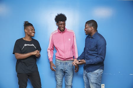 Three guys standing against a blue wall laughing